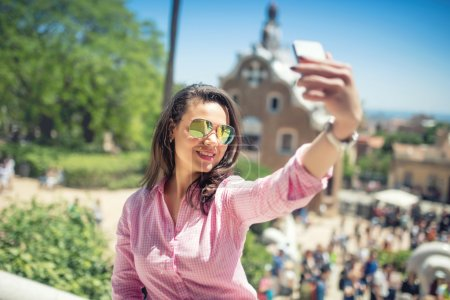 modern concept of photography, young woman taking selfie with mobile phone and posting in on social media.