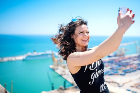I love selfie! portrait of beautiful brunette girl taking photographs of herself, selfies, on the shore at seaside. modern concept of social life, instagram