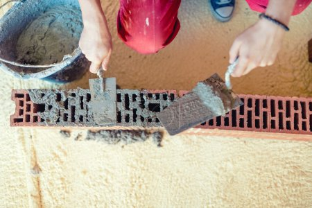 close-up of Construction worker building walls and fixing bricks with mortar and putty knife