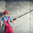 Industrial worker with plastering tools renovating...