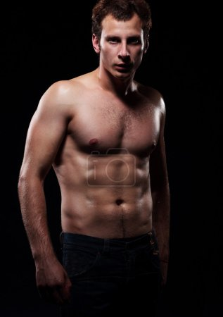 Body of a young muscular man,  studio dark background.