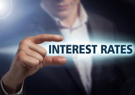 Businessman presses button  interest rates on virtual screens. B