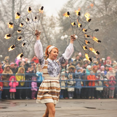 Orel, Russia - March 13, 2016: Maslenitsa, Pancake festival. Fire dancer girl in Russian clothes performing for crowd