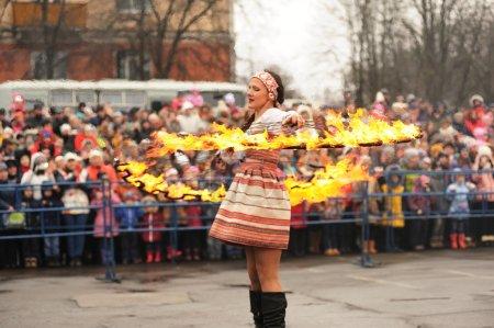 Photo pour Orel, Russie - 13 mars 2016 : Maslenitsa, festival Pancake. Fille danseuse de feu en vêtements russes performant pour la concentration sélective foule - image libre de droit