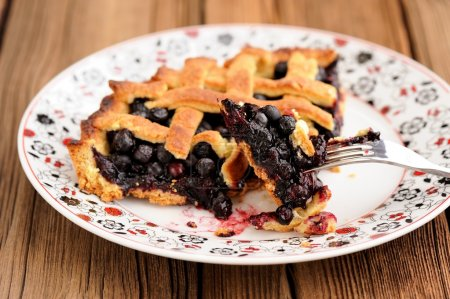 Piece of fresh homemade lattice pie with whole wild blueberries