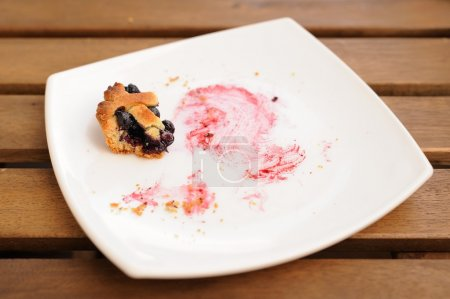 Remains of homemade blueberry pie in square white plate