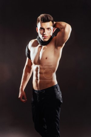 Sexy young man with a naked torso on a dark background