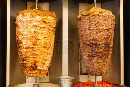 Photo pour De délicieuses tranches de viande de poulet et d'agneau shawerma brochettes de restauration rapide tournent côte à côte sur une broche. C'est la viande sandwich commune trouvée dans la restauration rapide au Moyen-Orient . - image libre de droit