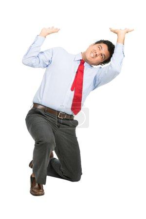 Photo pour Un homme d'affaires latino stressé en vêtements d'affaires sur le genou en utilisant les bras poussant vers le haut, résistant contre le poids imaginaire écrasant, objet soumis à un stress intense, ressentant une pression. Isolé sur fond blanc - image libre de droit