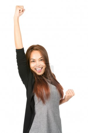 Photo for Ecstatic, good looking Asian woman in casual clothes, yelling, celebrating with winning arm raised, fist thrust in air looking at camera with euphoric smile. Thai national of Chinese origin. Half - Royalty Free Image