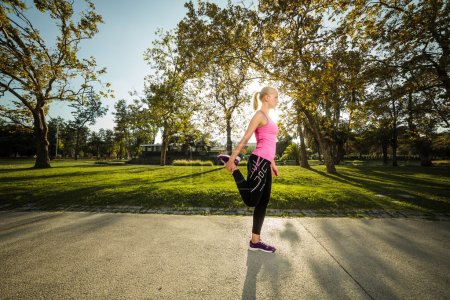 Woman training in urban park at sunset