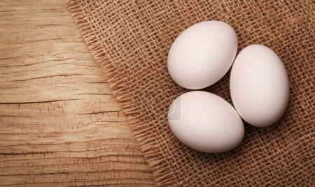 Photo for White eggs on burlap over wooden background - Royalty Free Image