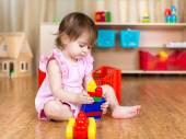 Dítě dívka si hraje s hračkami blok, vnitřní
