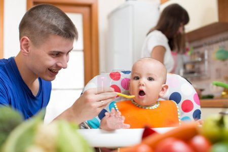 Young dad feeding his baby and mom cooking at kitchen