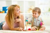 Cute woman and kid playing together indoor