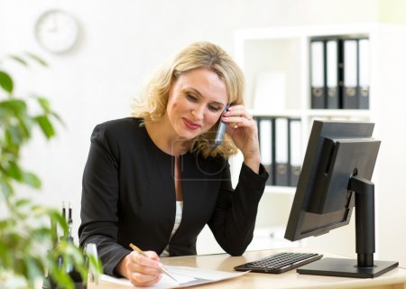 Smiling middle-aged businesswoman working in office