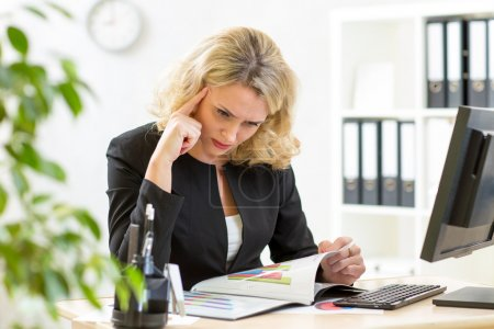Middle-aged business woman working in office and examining reports