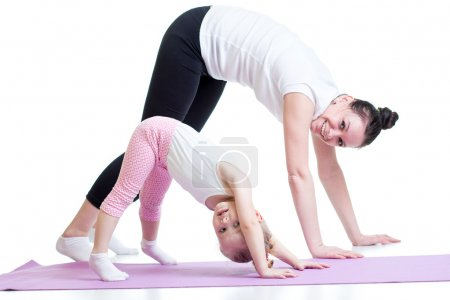 Yoga for woman and child. Mother and kid do fitness exercise