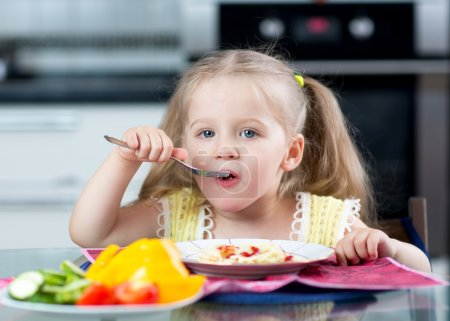 kid eating spaghetti with vegetables in nursery