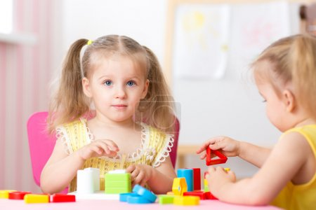 children play educational toys in preschool