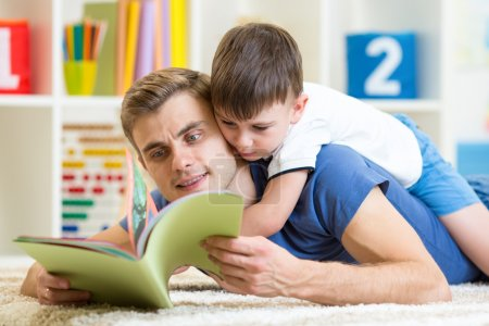 father teaches reading book to kid