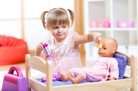 little girl playing doctor with her newborn baby doll in room