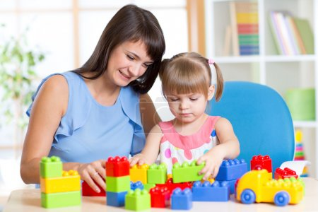 mother and kid play with toys at home