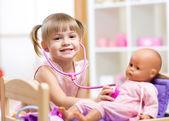 Dítě hrající doktor roli hra examinating panenku pomocí stetoskopu sedí v koutku doma, školy nebo školky