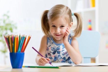 Cute little preschooler child drawing at home