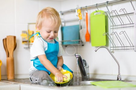 Child washing up in a domestic kitchen