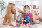 Kluk holka hraje s vnitřní vzdělávací hračky. Šťastná matka při pohledu na její chytrá dcera