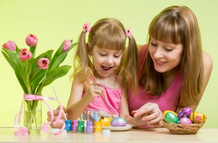 Happy mother and kid daughter decorate Easter eggs