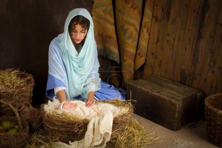 Photo for Teenager girl playing the role of the Virgin Mary with a doll in a live Christmas nativity scene - Royalty Free Image