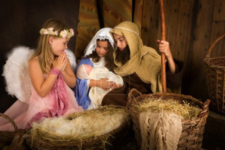 Photo for Little 7 year old angel visiting a nativity scene reenacted with a doll - Royalty Free Image