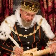 Old king signing a new law with a feather quill...