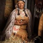 Weathered mature tribal female storyteller talking...