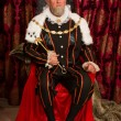King in tudor costume sitting on his throne holdin...
