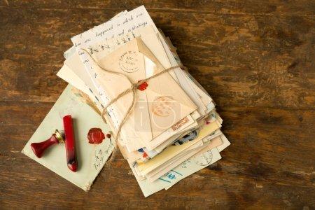 Photo pour Sceau de cire à côté d'un paquet de vieilles lettres sur une table en bois antique - image libre de droit