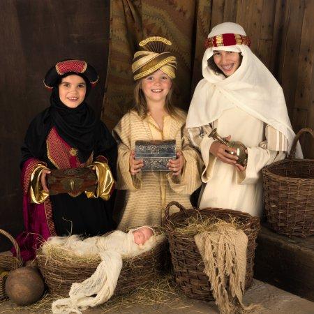 Photo pour Trois jeunes filles jouant comme sages avec une poupée dans une crèche de Noël - image libre de droit