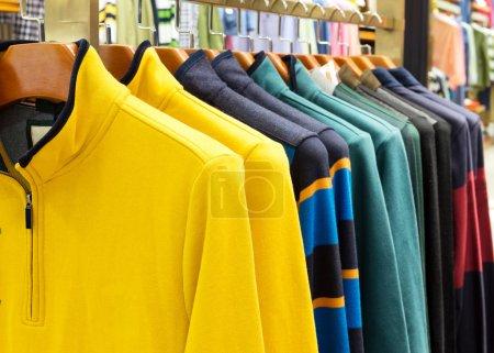 Photo pour Une ligne de tee-shirts colorés ligne suspendus sur des cintres - image libre de droit