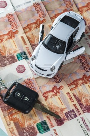 White toy car on the background of banknotes