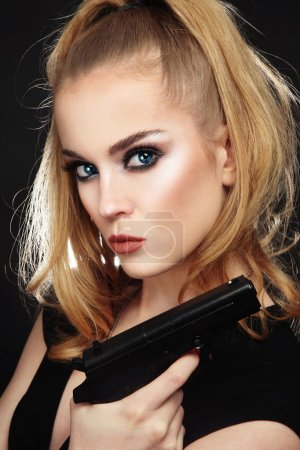 Photo for Portrait of young beautiful sexy blonde woman with stylish make-up holding a pistol in her hand - Royalty Free Image
