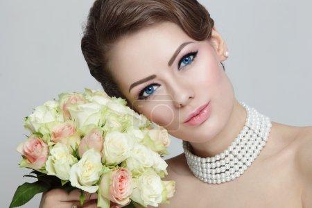 bride with stylish hairdo holding bouquet
