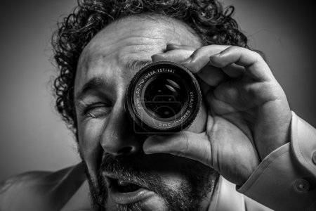 Photo for Man photographer with lens on eye making funny face expression - Royalty Free Image