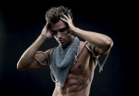 Attractive naked man with abdominal, chain mesh medieval neck wi