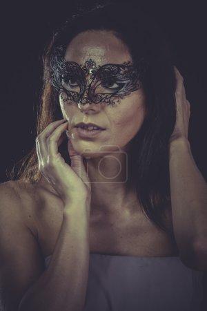 Woman in black venetian mask
