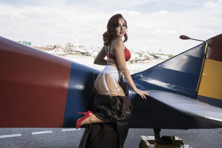 woman in Second World War style with vintage aircraft