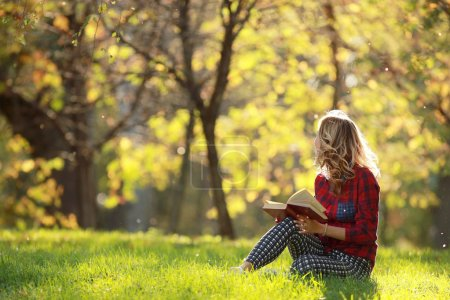 Photo pour Jeune fille dans un parc ensoleillé lisant un livre - image libre de droit