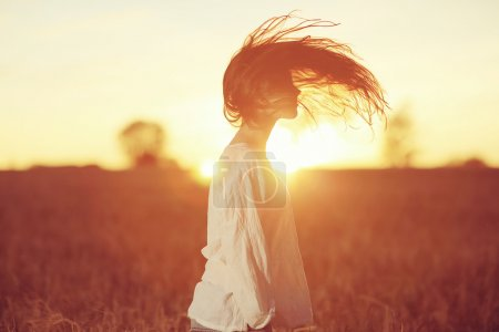 Photo for Girl with long hair at sunset in the field - Royalty Free Image
