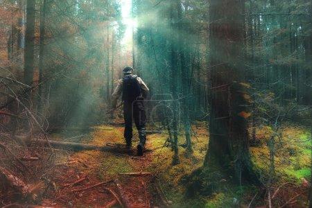 Traveler in autumn mystical forest